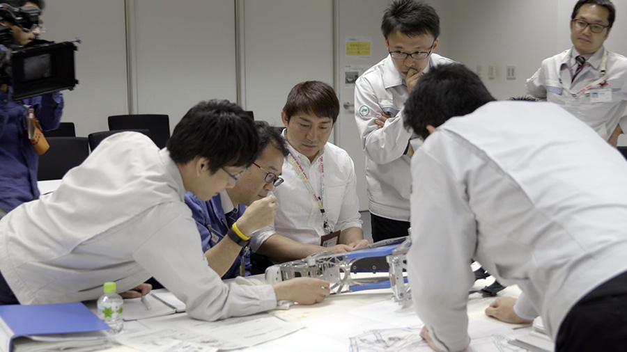 Engineers engage in discussion over prototype model